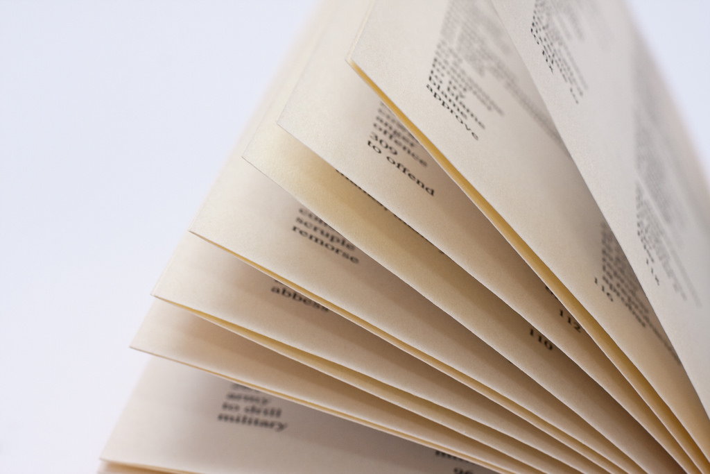 Macro of yellowed pages of a photography glossary flipping up in the air isolated against a white background.