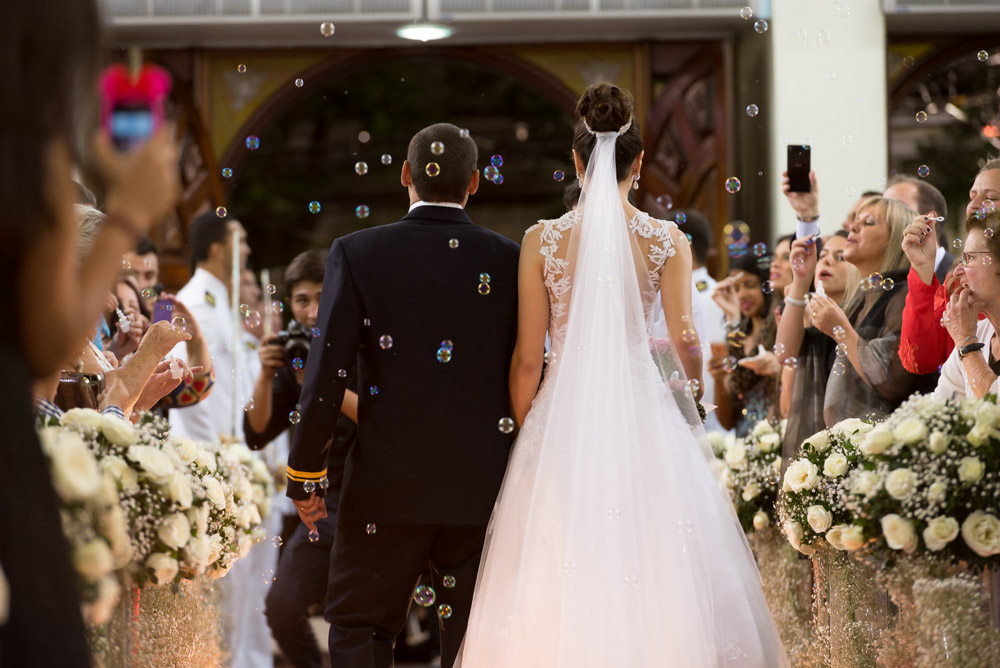 Example image of a couple leaving their wedding ceremony to some bubbles from far away with the Nikon 70-200