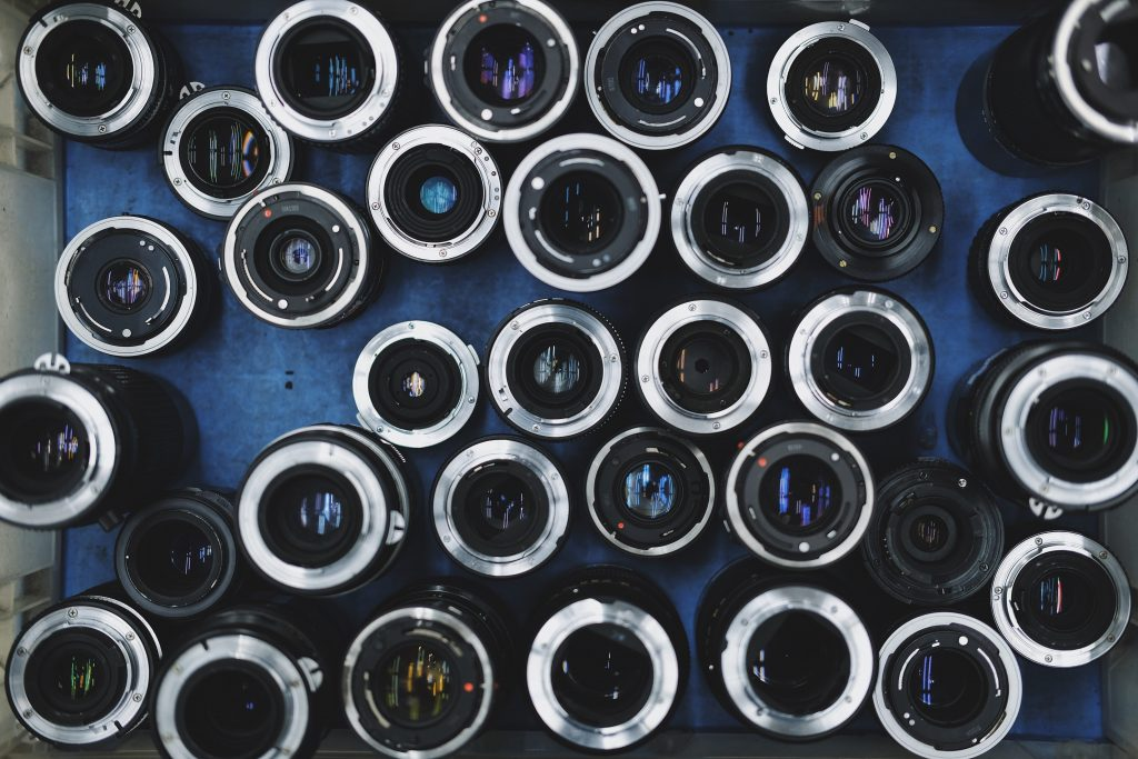 Cover image for article about the best Nikon lenses for weddings of a bunch of Nikon lenses laid out on a table
