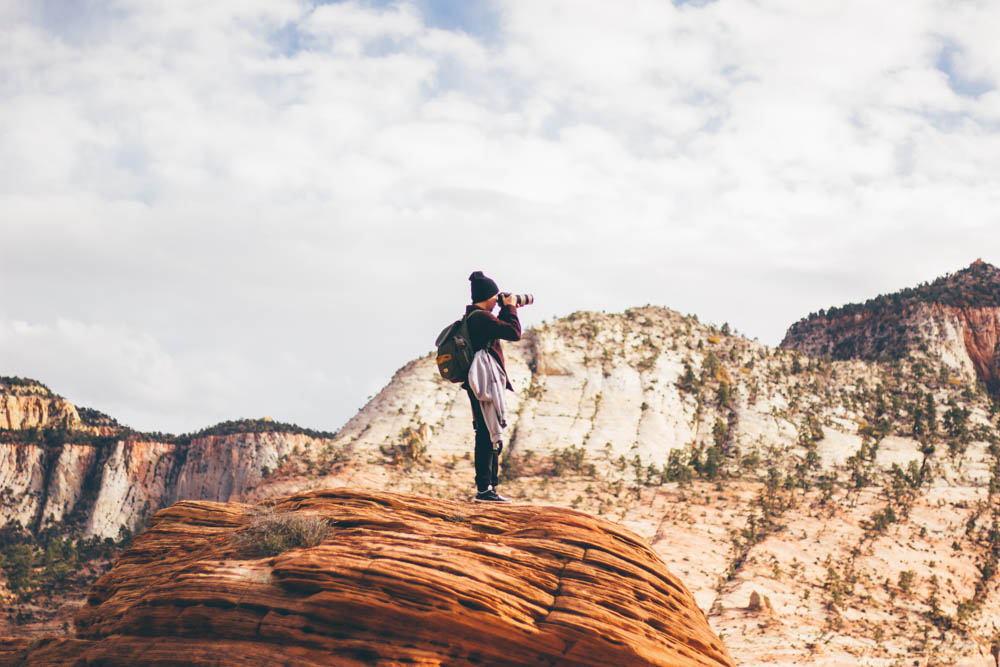 Guy shooting a landscape photo in the middle of a desert canyon