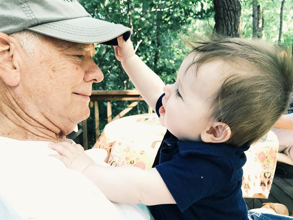 Image of baby grabbing grandpa's hat in outdoor setting shot with the iPhone 7 Plus