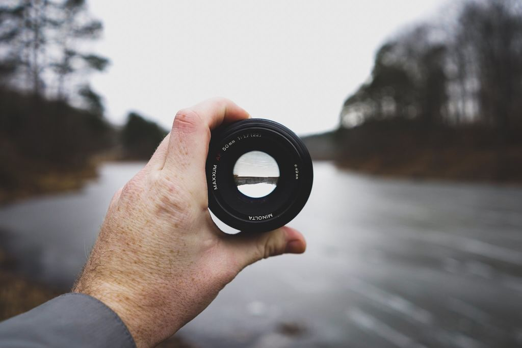 Image of person holding up a lens with the aperture open