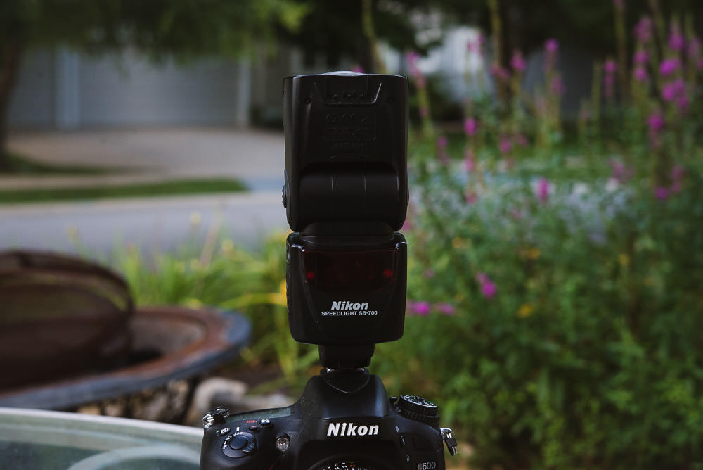 Image of the Nikon SB-700 Hot Shoe Flash on Top of a Nikon camera with the flash head pointed up, as you would do when you want to bounce flash