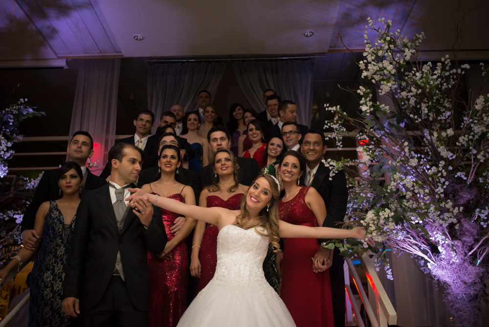 image of bride smiling and joking in front of wedding group