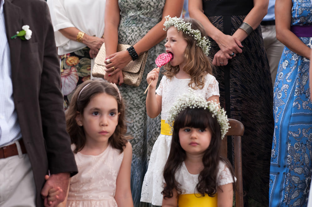 Image of girls at a wedding ceremony, one of which is licking a lollipop