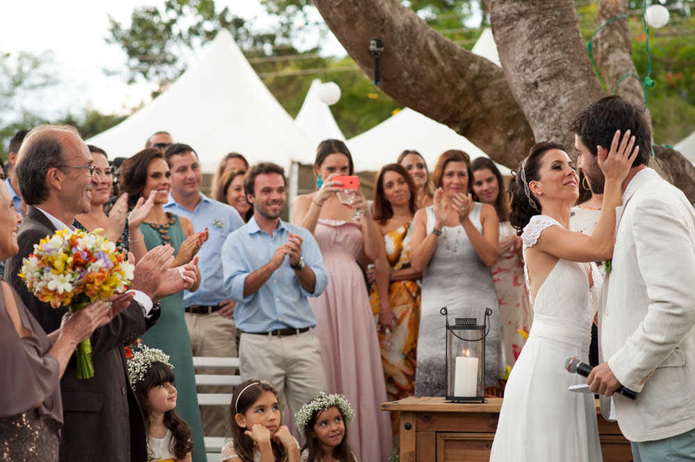 Wedding photography image of bride putting her hand on the groom's cheek while the attendees applaud