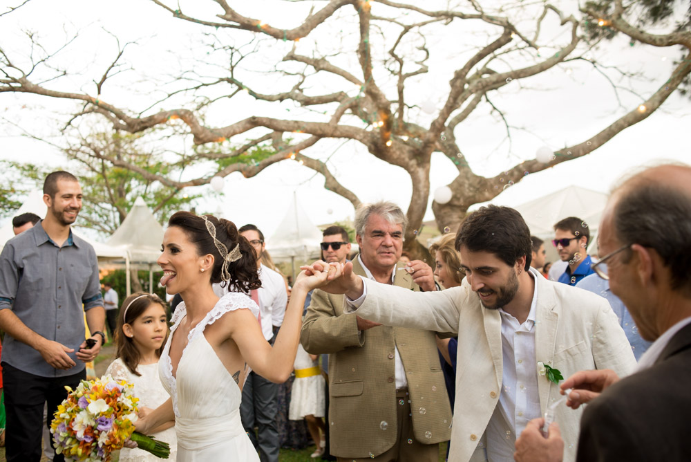 Image of a bride and groom holding hands as they leaving their outdoor wedding ceremony
