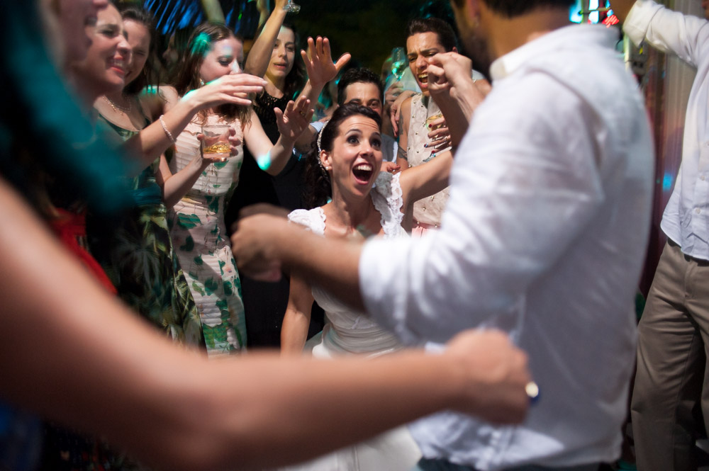 Image of bride and groom during exciting part of song dancing with each other and laughing