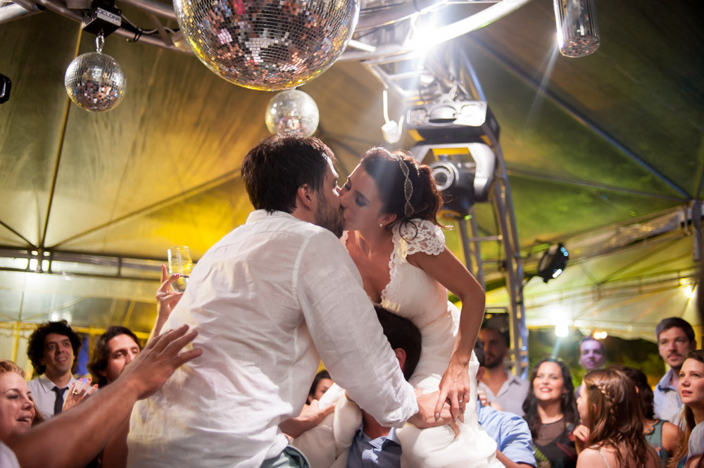Picture of a bride and groom on the shoulders of guests on their wedding reception dance floor kissing