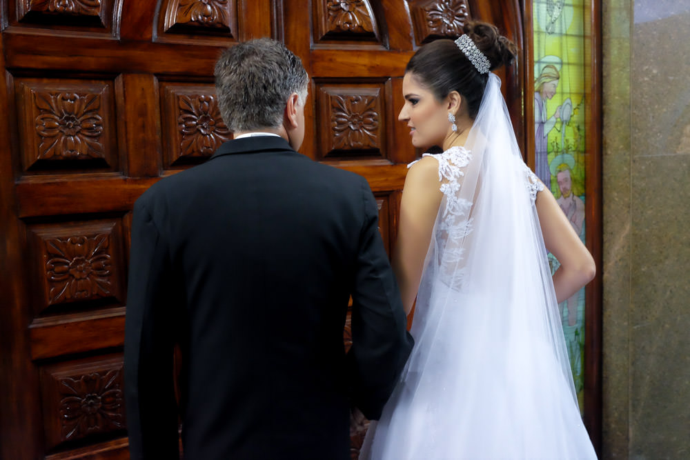 Wedding photography picture of a bride looking at her father before they walk down the aisle