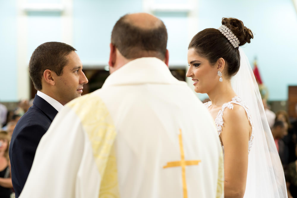 Up-close image of a bride and groom looking at each other in front of their priest while standing at the alter getting married