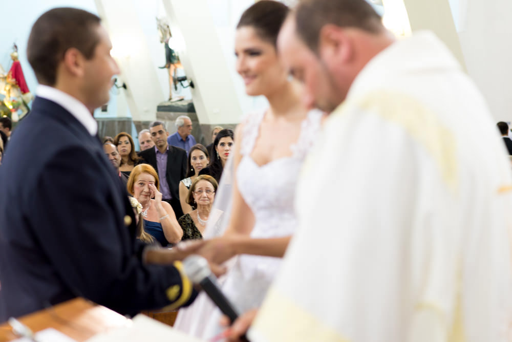 Picture taken during a wedding ceremony of a bride and groom giving their vows while a woman in the audience wipes a tear