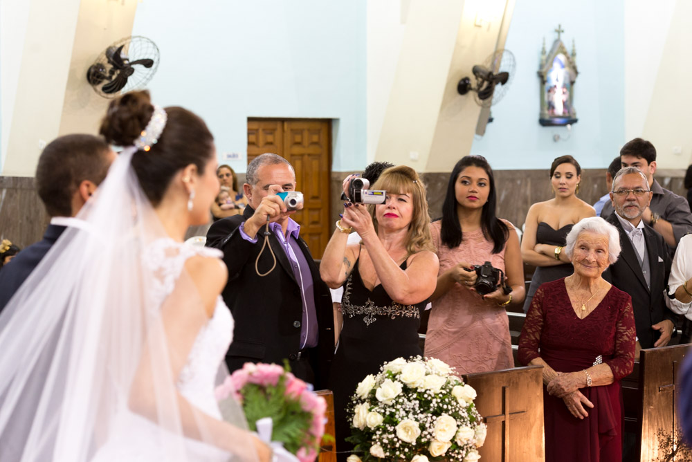 Image of a bride and groom shoot from an angle about to walk out the church after ceremony with grandma looking on and smiling