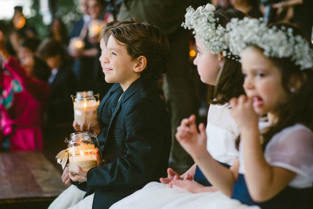 Image of kids watching wedding ceremony, one of whom is a boy holding a candle and smiling