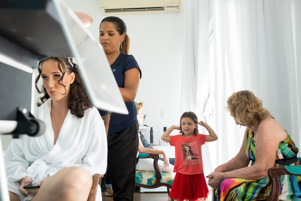 Image showing a bride getting her hair done while her niece plays in the background with another relative