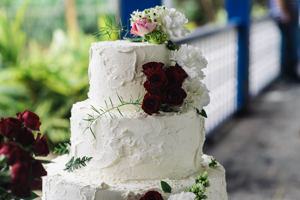 Up close image of a white wedding cake with white, red and pink flowers decorating it