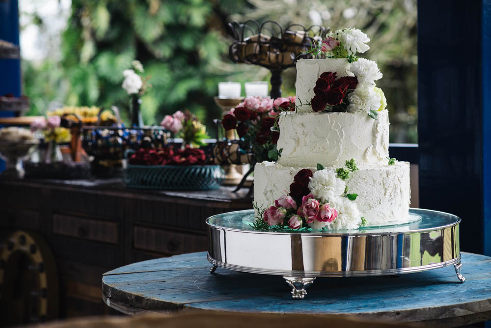 Image of a white wedding cake set up outdoors with flowers on it