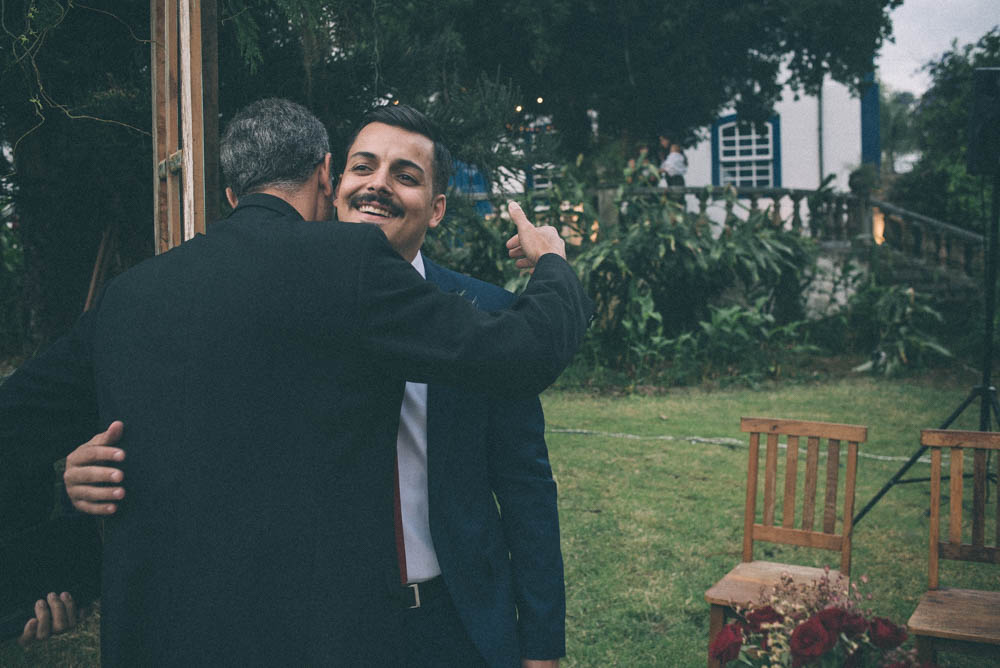 Image of a groom hugging a priest before the start of a wedding ceremony