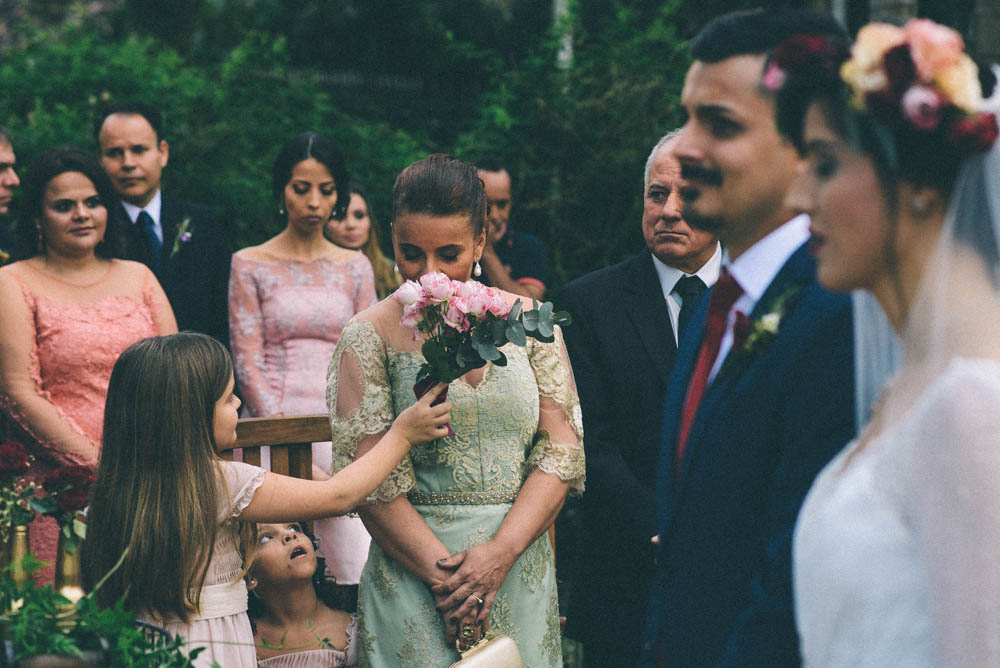 Wedding photography photo during a ceremony with the bride and groom to the right of the frame slightly out of focus and with a flower girl telling her mom or aunt to smell the flowers