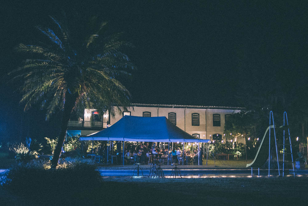 Image of a wedding venue at night with a pool, a palm tree, and a tent where people are partying under for the wedding reception