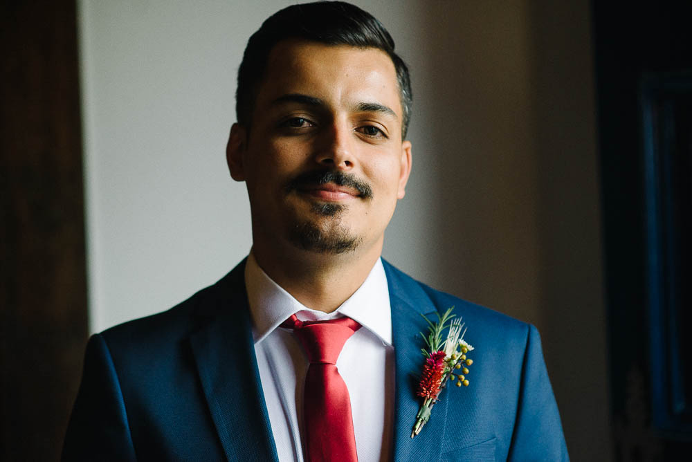 Image showing an example of an indoor photography tip without flash of a groom in a blue suit with a red tie and a flower lapel before his wedding ceremony shot with window light