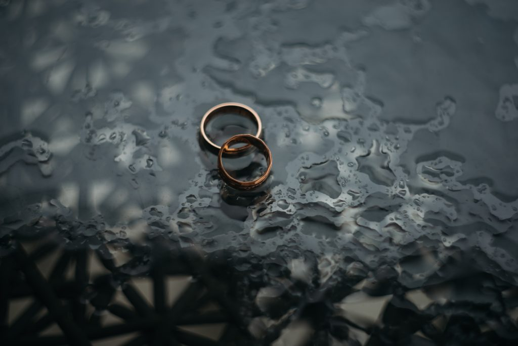 image example of some wedding rings on a wet surface for blog post about how to find wedding photography assistant jobs