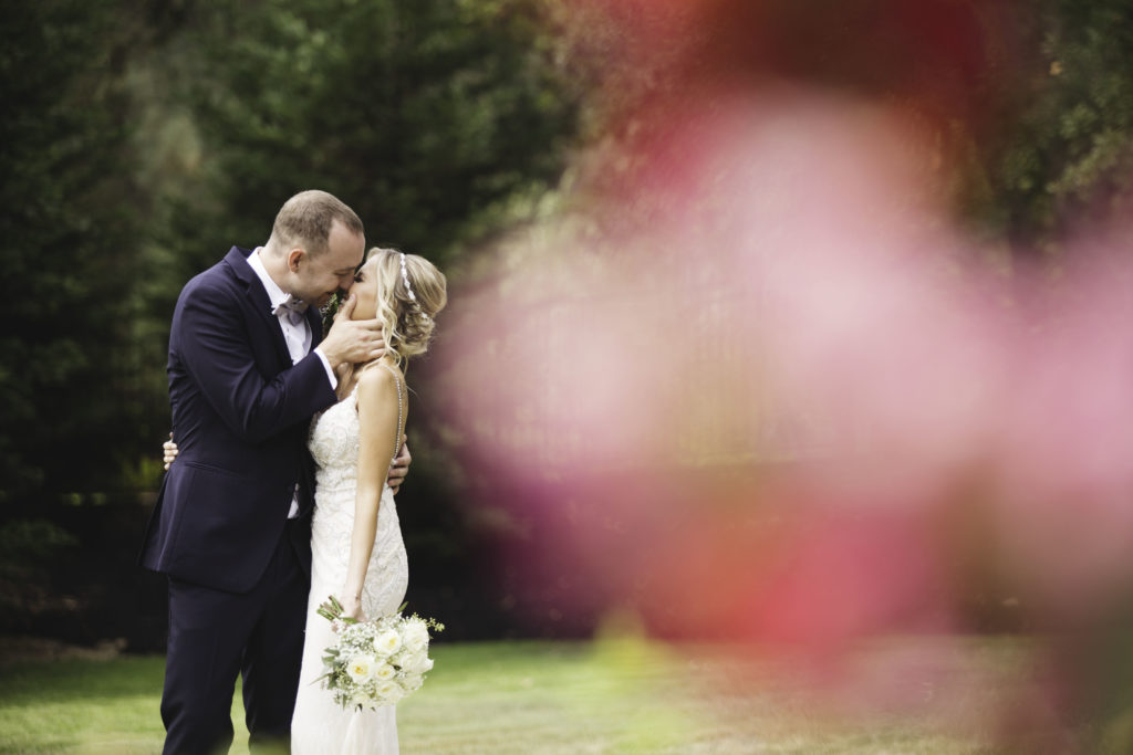 image of a bride and groom on their wedding day kissing with a red flower in the foreground