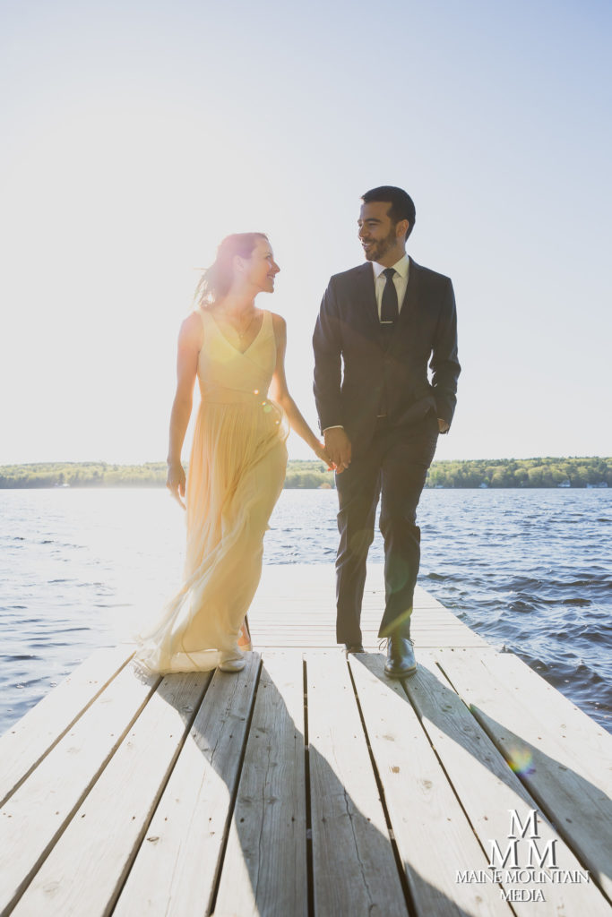 photo of a couple on a lake dock looking each other in the eyes and backlit by the sun by photographer Paul Friedman