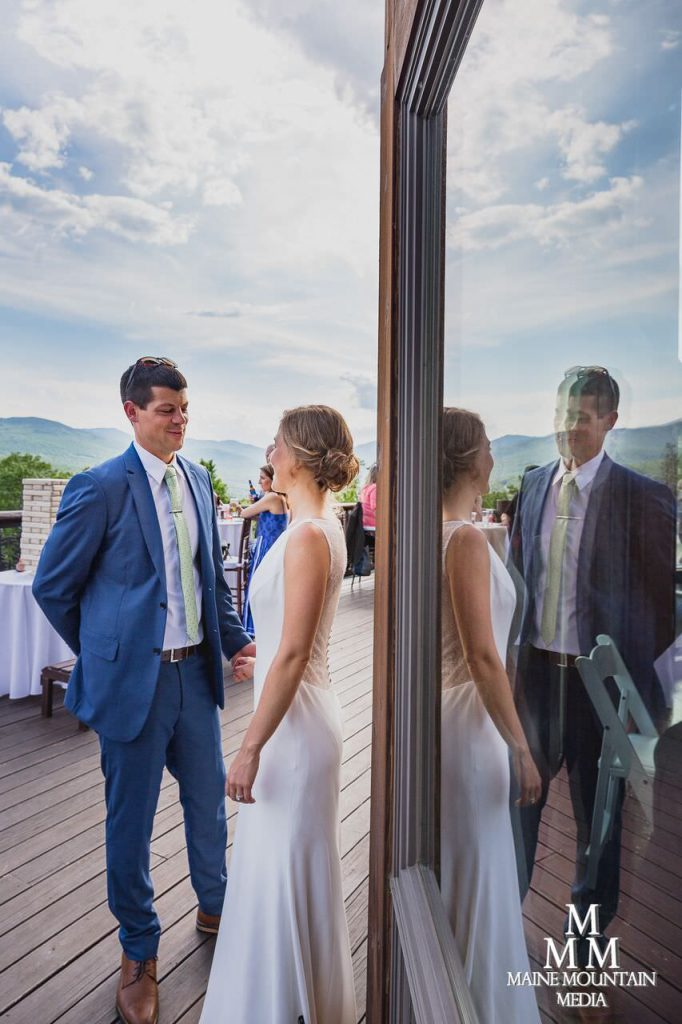 Picture of a bride and groom looking at each other outside in the sun after their ceremony as their reception is about to start and being reflected in a window