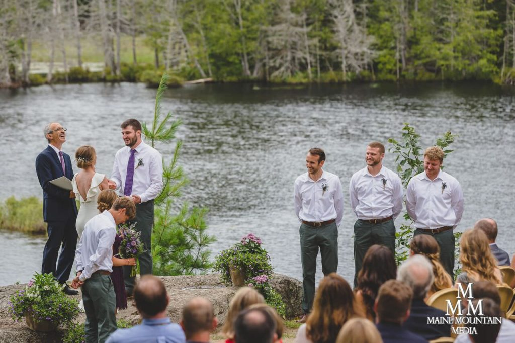 Image of a wedding on a lake of groomsmen look on as the bride and groom of the wedding exchange vows and share a funny moment