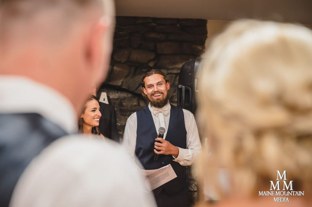 Photo of best man giving a speech from the angle of the bride and groom
