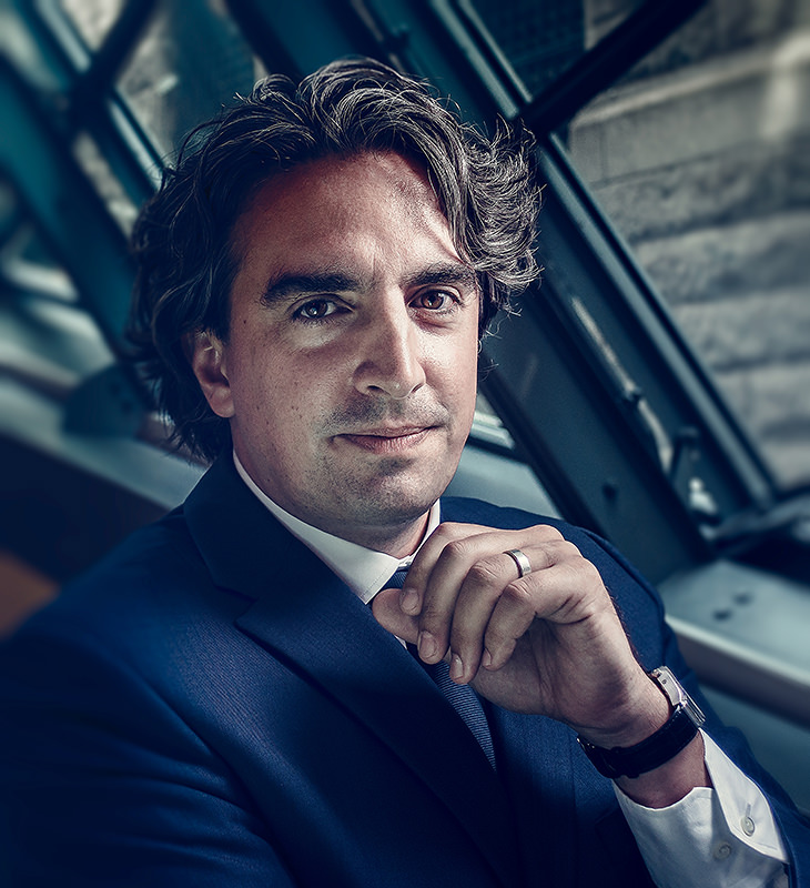 Image of a corporate portrait of a man with medium-length curly hair in a blue suit, a watch on, a ring in front of a window being lit with window light