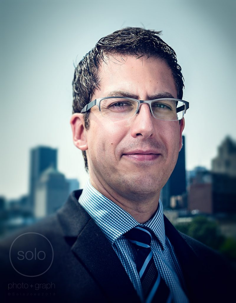 Image of a corporate employee in a suit and glasses straight on looking at the camera in front of a cityscape of buildings