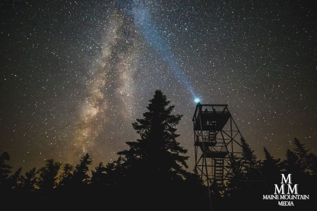 Nightscape image of a park ranger tower with a starry sky