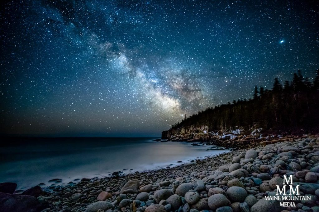 Image of a nightscape of a rocky beach with a blue starry night sky