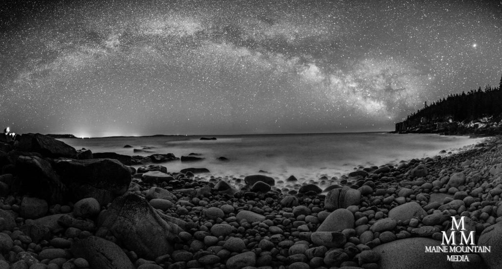 Black and white nightscape picture of a rocky beach with a starry sky