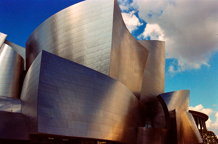 Cityscape photo of the Disney Hall at sunset with unique colors seen in the metal