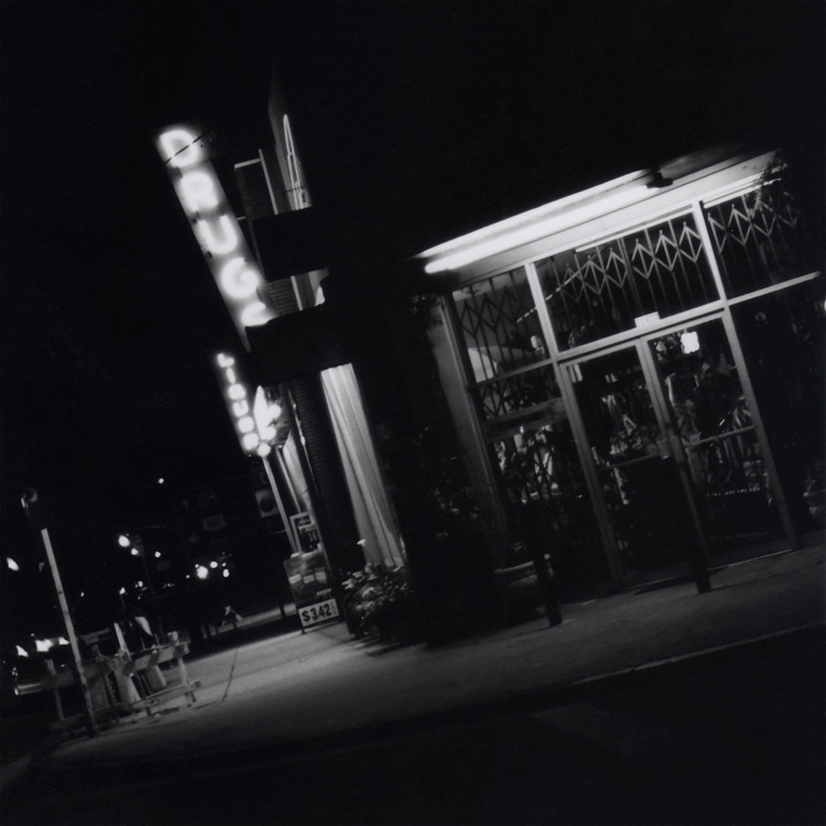Black and white cityscape of a drugstore at night