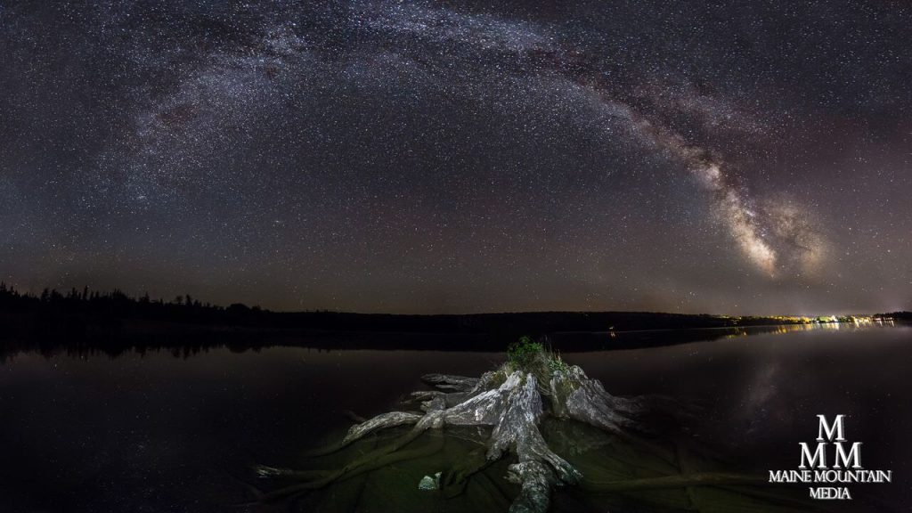 Nightscape image of a stump in a lake and a starry night sky