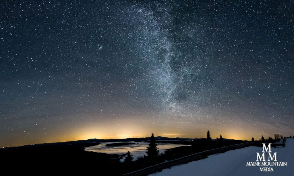 Picture of a starry night sky overlooking a river and with snow on the ground