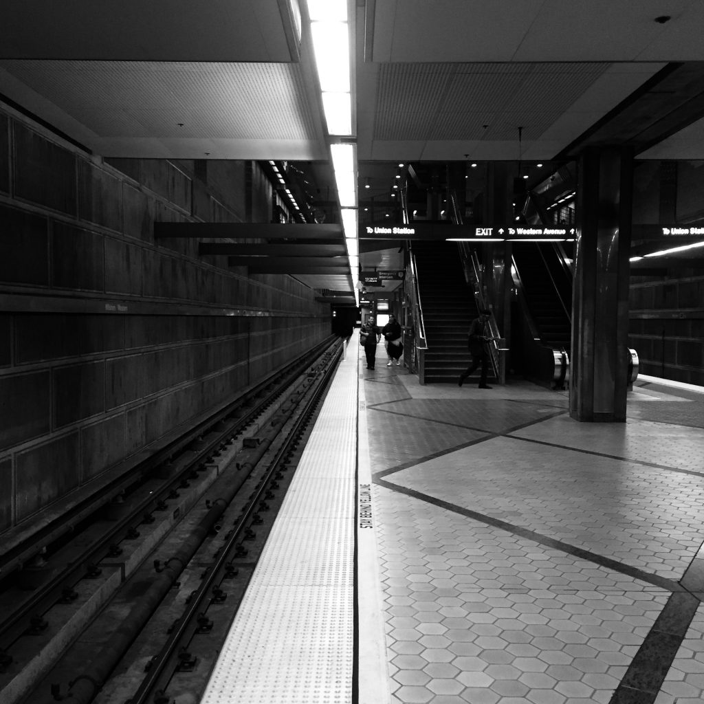A dark black and white photo in a subway with a leading line down the middle of the frame