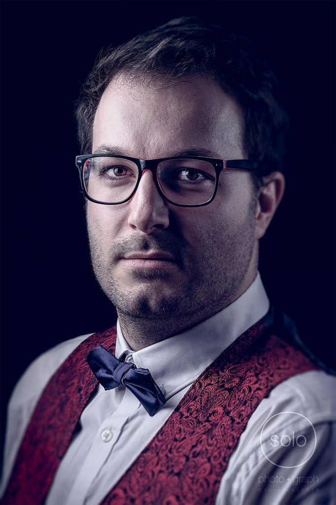 Corporate portrait of a main with glasses and a bow tie and a black background that was actually white