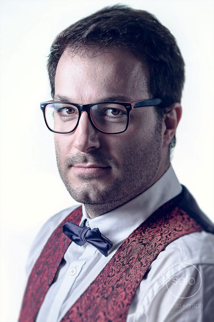 Photo of a corporate portrait lit with a pure white background of a man with brown hair, glasses, a bowtie, and a red vest