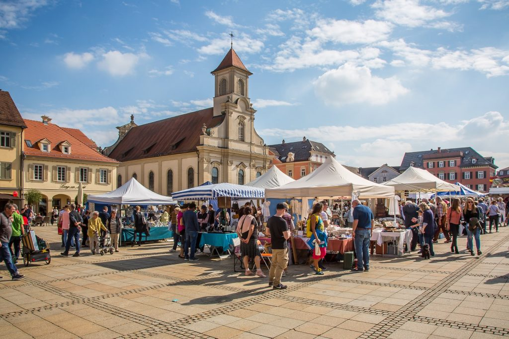 Image of an outdoor market with the sun shining and a bright blue sky with a few clouds, serving as an example as to finding marketplaces to sell your landscape photography