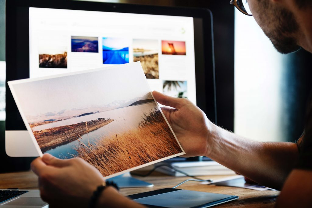 Image of someone looking at a printed picture of a landscape