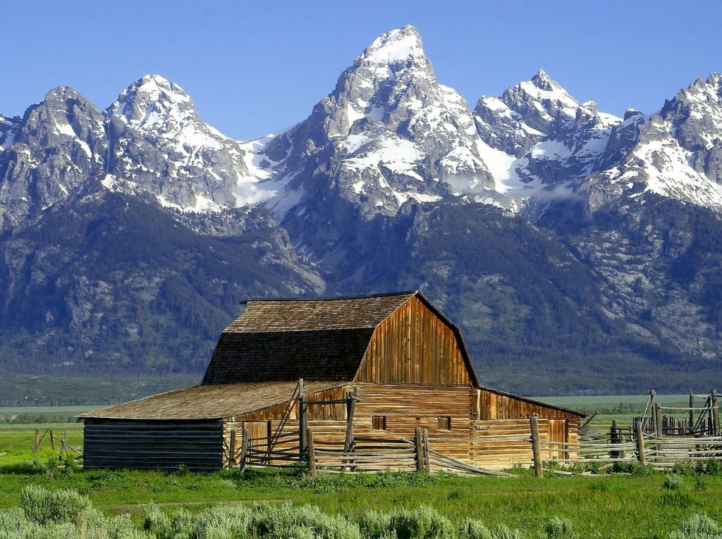 Image showing how to sell landscape photography work with a landscape of a barn in green grass in front of a mountain range and a blue sky
