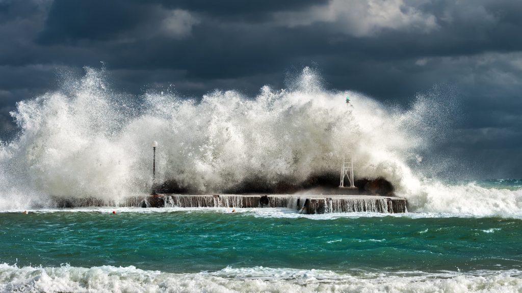 Image of a big wave crashing on some rocks