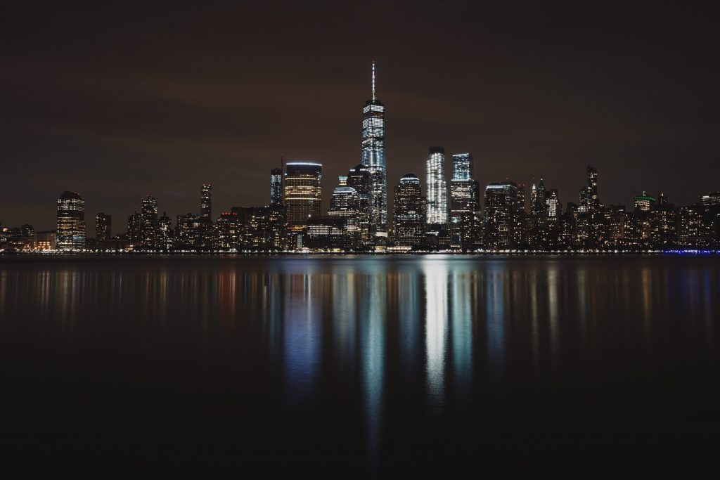 Photo of the New York City skyline and the lights from the building being reflected in water as an example of white balance for night sky photography