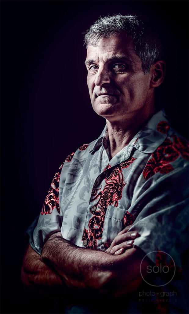 Portrait of a man with a blue button down short sleeve shirt lit with creative portrait rembrandt lighting