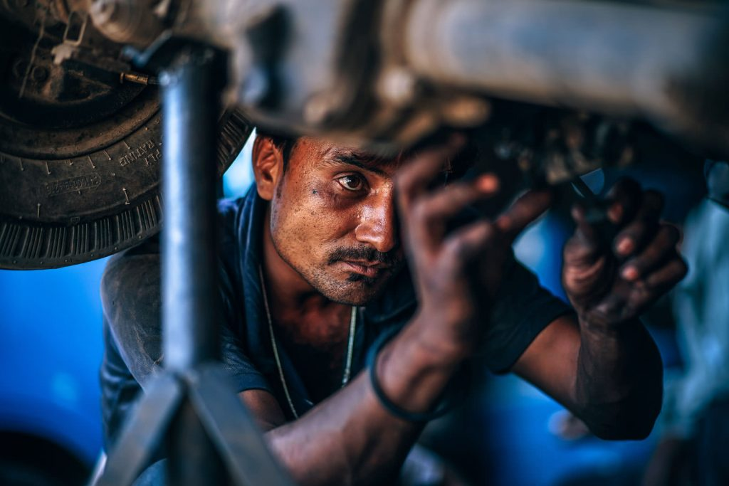 Creative candid portrait of a man working on a car